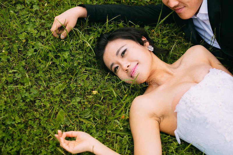 Newly-married couple Lie on green grass. In field royalty free stock image