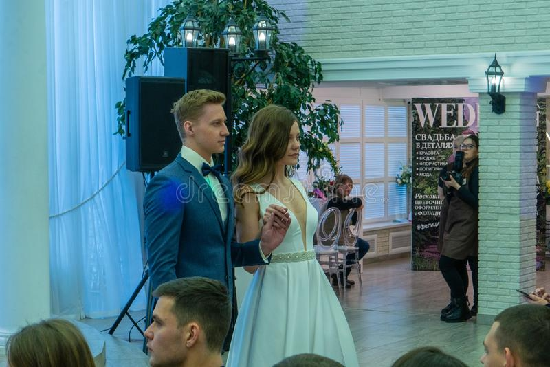 A newly married couple models passing by a podium. At the exhibition Wedding hassle 2019 took place in Kirov, Russia royalty free stock images