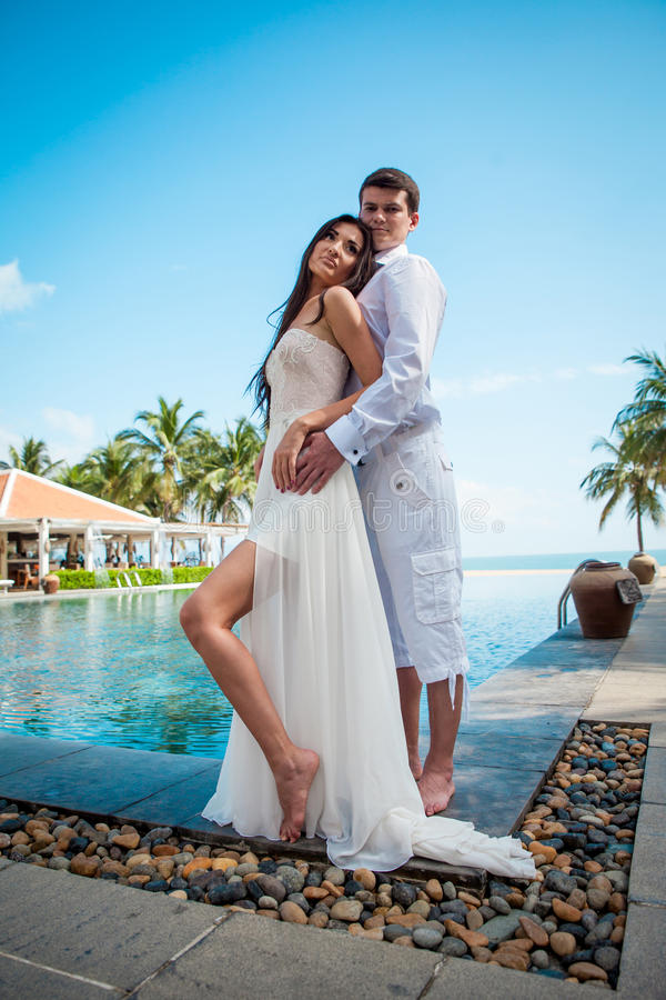 Newly married couple after wedding in luxury resort. Romantic bride and groom relaxing near swimming pool. Honeymoon. stock image