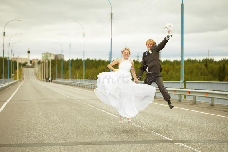 Newly married pair jumps on highway royalty free stock photography