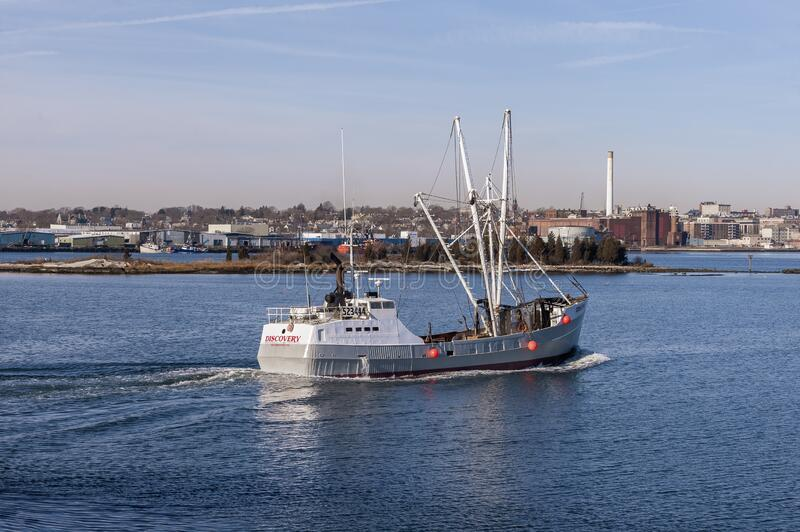 Newly painted eastern rig scalloper Discovery crossing New Bedford inner harbor royalty free stock photography