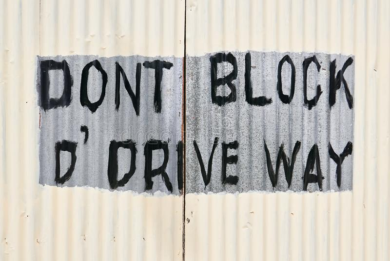 Newly painted gate with writing `Don`t block the driveway royalty free stock photos