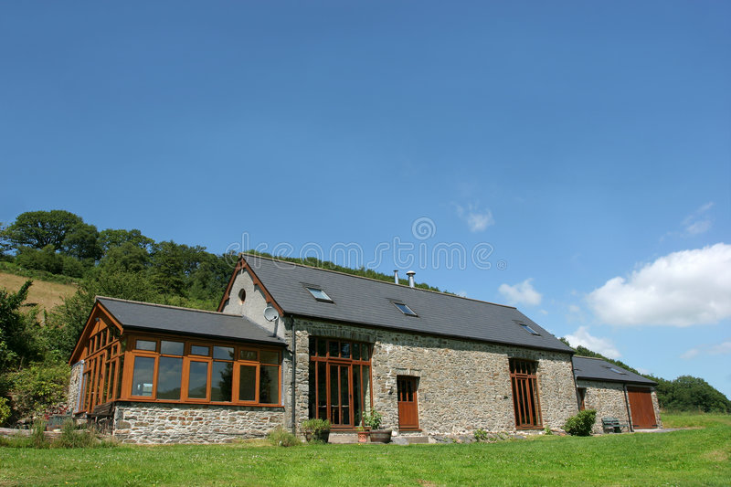 Newly Restored Barn. Newly restored residential stone barn with a slate roof in rural countryside against a blue sky stock photography