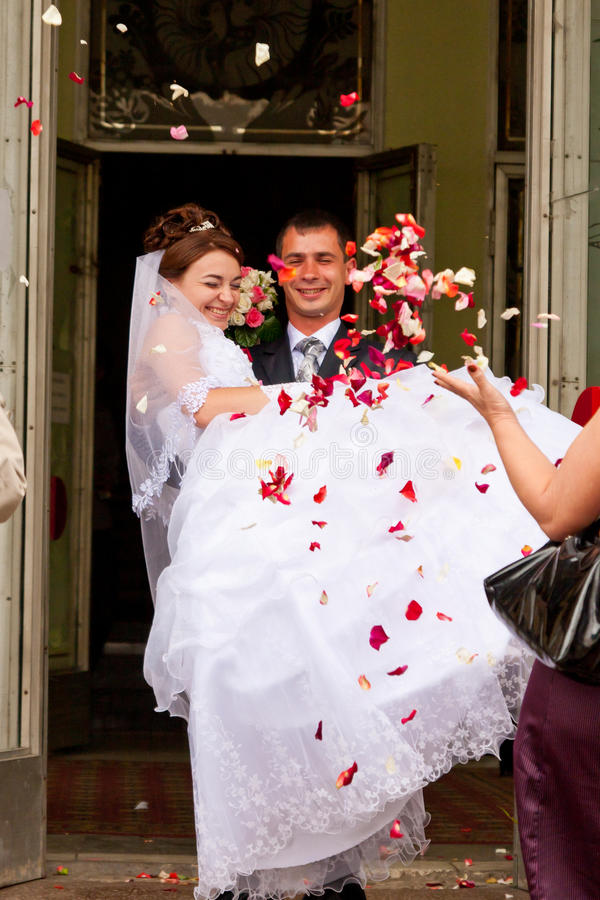 Newly wed happy couple. Being showered in rose petals royalty free stock images