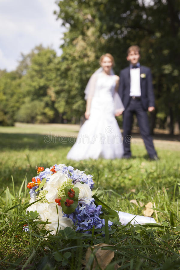 Newly wed holding hands, wedding bouquet in the foreground stock image