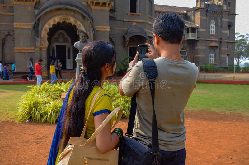 Newly wedded couple taking a perfect click of a monument or old architecture with their mobile phone camera stock image