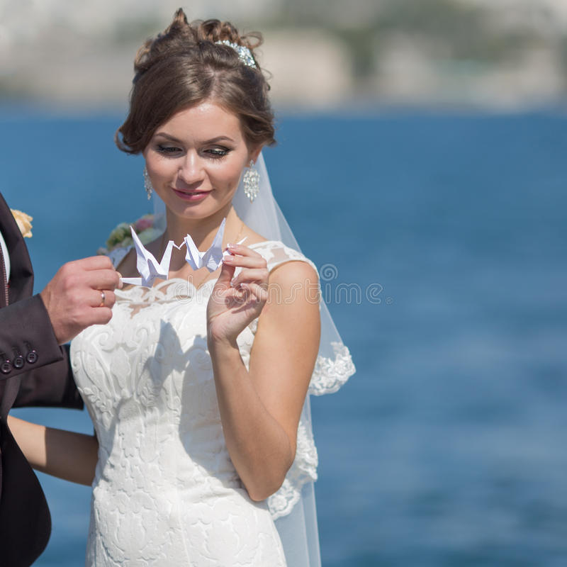 Newly wedded playing with origami cranes stock photo