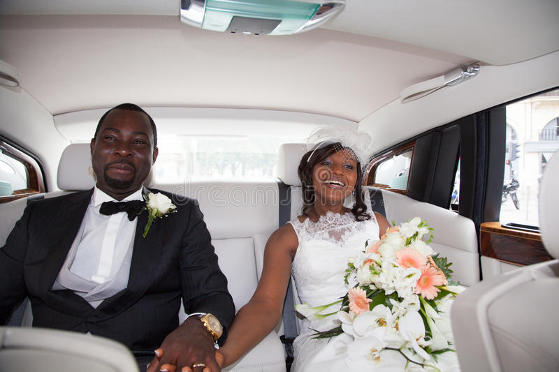 Newlywed african couple sitting in the car royalty free stock photography