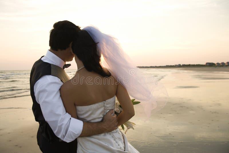 Newlywed Couple on Beach. Rear view of a newlywed couple hugging on beach. Horizontal shot stock image
