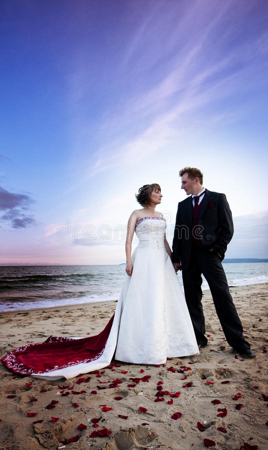 Newlywed couple on beach. Newlywed couple on sandy beach under cloudscape with sea in background stock image