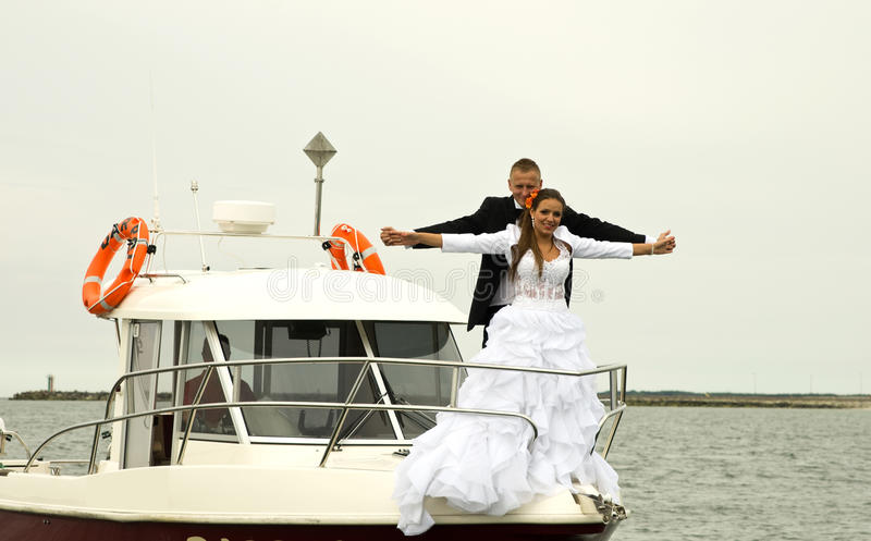 Newlywed couple on boat. Happy newlywed couple on boat posing in the style of the film Titanic stock photos