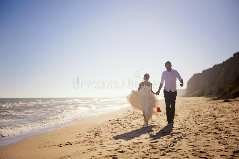 Newlywed couple celebrating marriage outdoors, running wed couple. Seascape, backlite royalty free stock photos