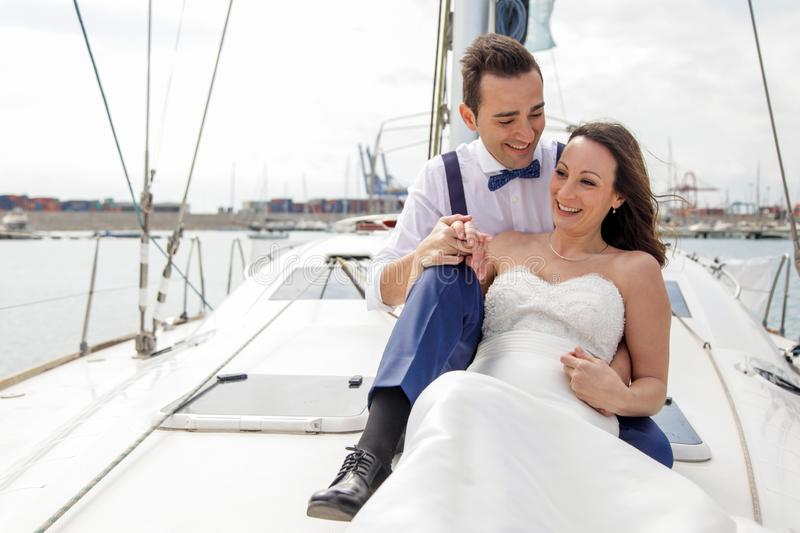 Newlywed couple enjoying their honeymoon aboard a sailboat. Newlywed couple having a ball on the deck of a sailboat in an European port royalty free stock image