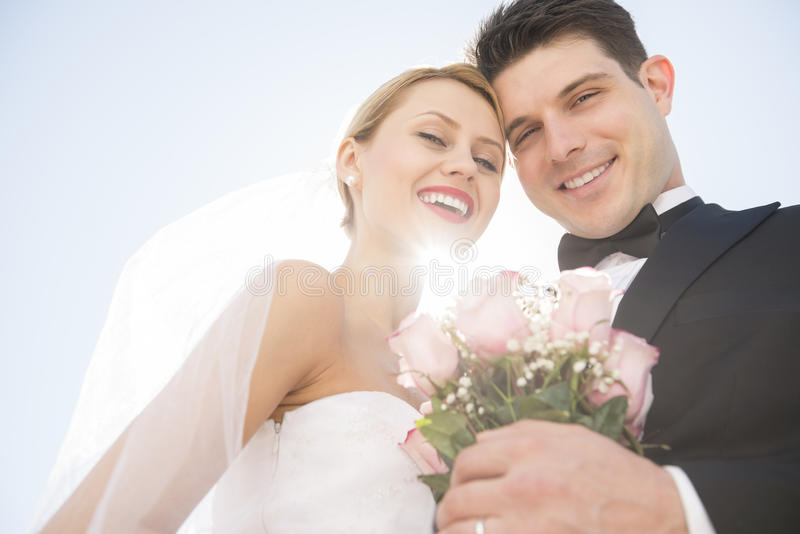 Download Newlywed Couple With Flower Bouquet Smiling Against Clear Sky Stock Image - Image: 32429877