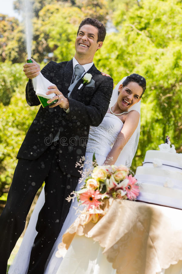 Newlywed couple with groom opening champagne bottle at park stock photos
