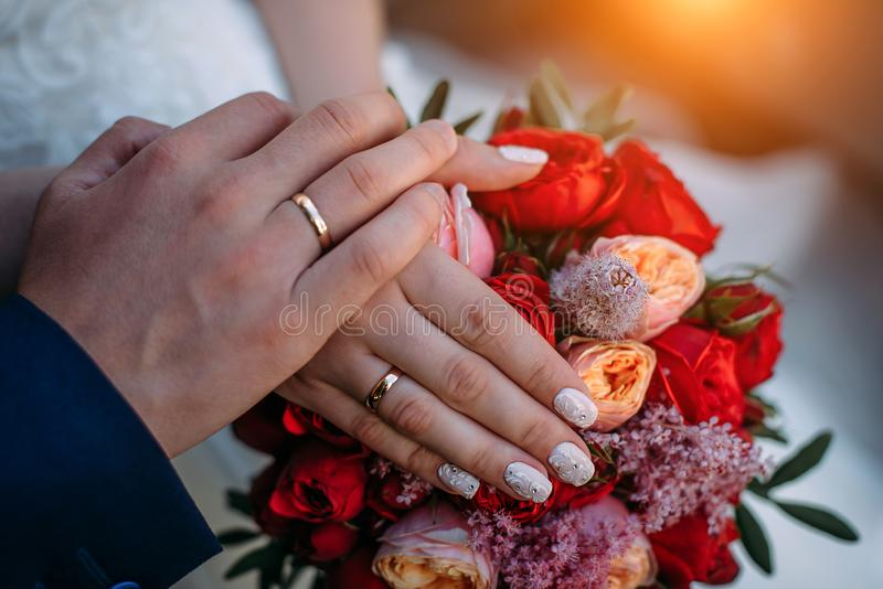 Newlywed couple holding hands and displaying wedding rings, close up. Hands and rings on the background of wedding bouquet stock photos
