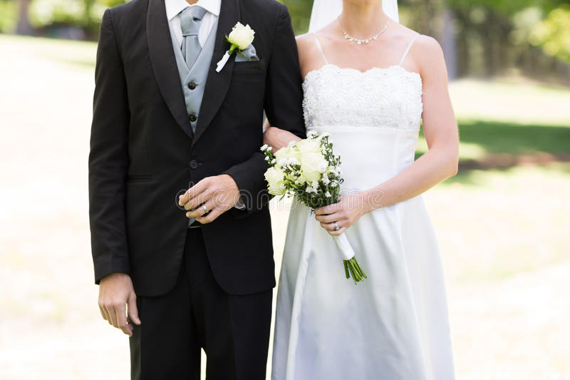 Newlywed couple holding hands in park royalty free stock photos
