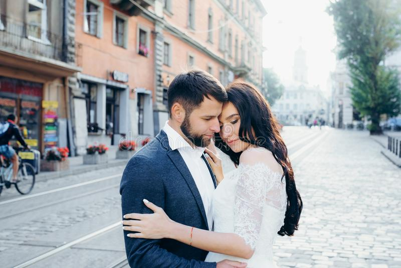 Newlywed couple in love is softly hugging in the town street. Sensual wedding portrait. royalty free stock images