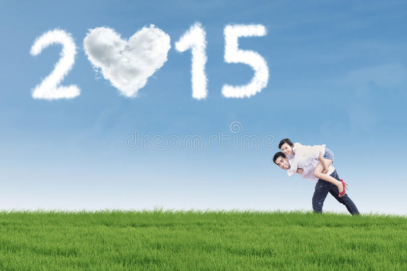 Newlywed couple on the meadow. Attractive asian couple piggyback on the meadow enjoy new year holiday stock photos