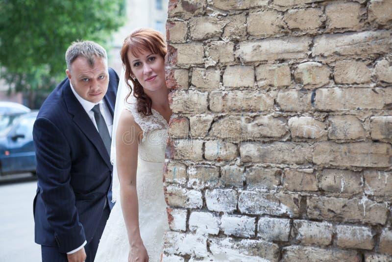 Newlywed couple peek around corner of brick wall, copyspace. Newlywed couple peek around the corner of brick wall, copyspace royalty free stock images