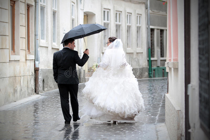 Newlywed couple in rain. Walking the urban streets with umbrella royalty free stock photo