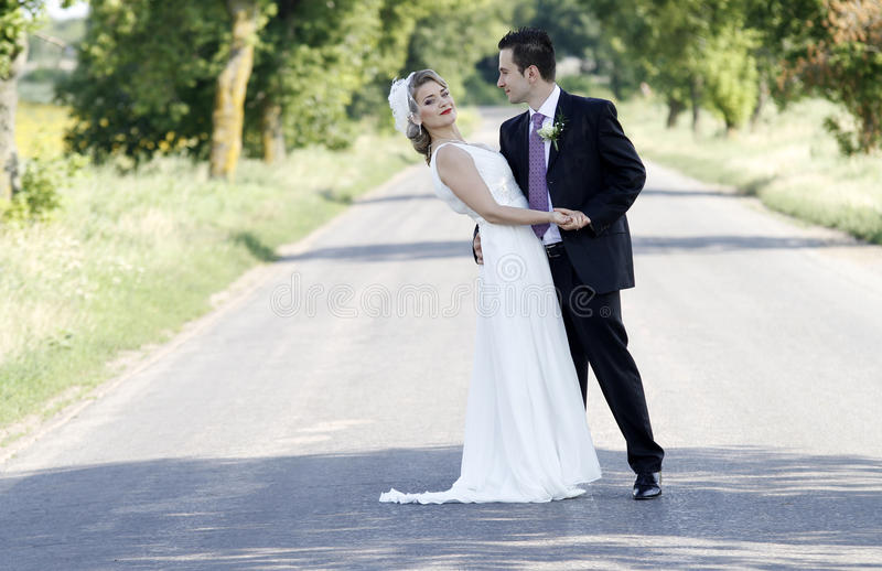 Newlywed couple on road. Newlywed young couple on road in countryside stock image