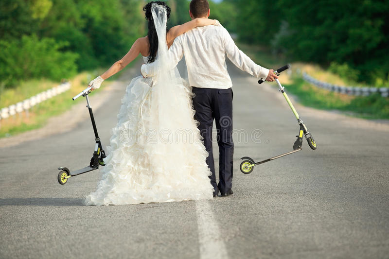 Newlywed couple with scooters stock photo