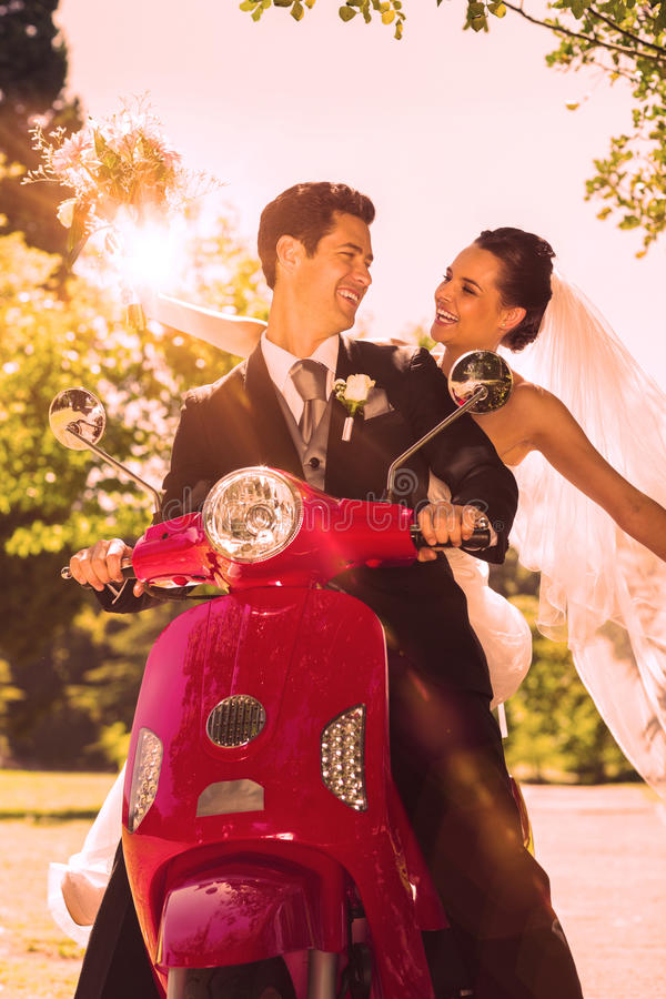 Newlywed couple sitting on scooter in park royalty free stock photography