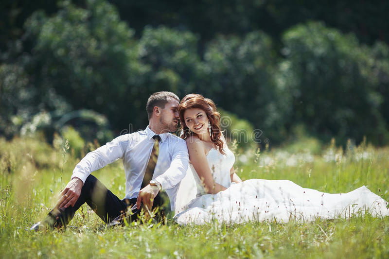 newlywed couple sitting & smiling in field royalty free stock photography