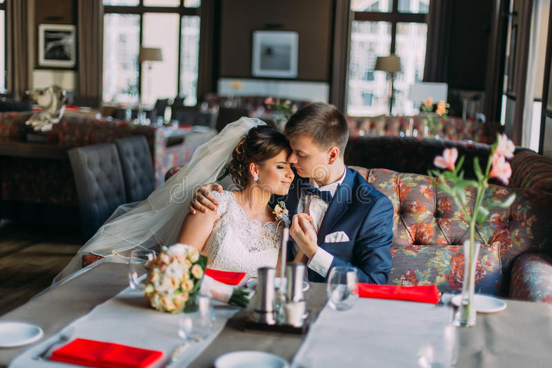 Newlywed enloved bride and groom holding each other while sitting on sofa. Luxury bright interior with big windows as stock photos
