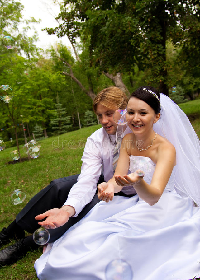 Newlywed with soap bubbles. Smiling happiness newlywed with soap bubbles stock images