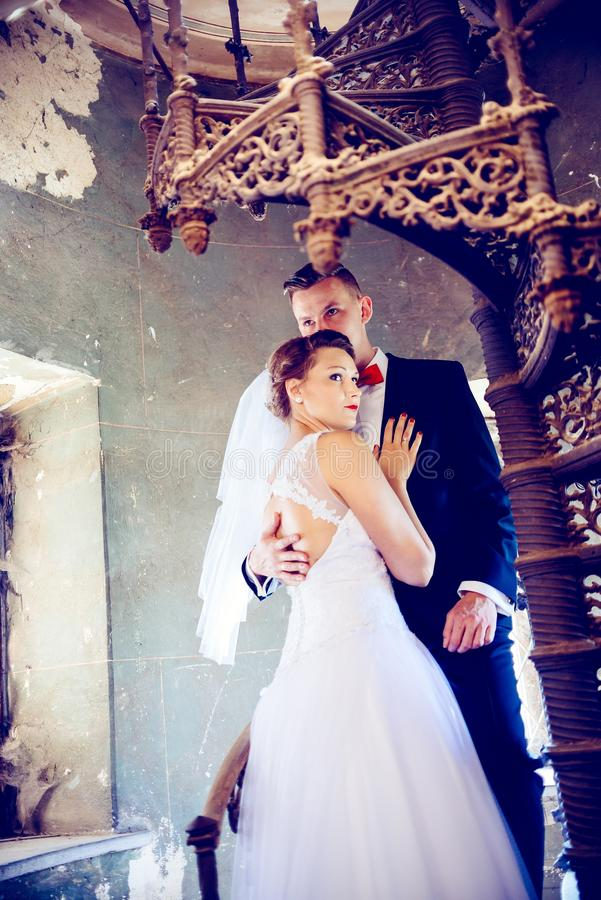 Newlyweds που αγκαλιάζει κοντά στα παλαιά σκαλοπάτια ευτυχής εκλεκτής ποιότητας γάμος ημέρας ζευγών ιματισμού στοκ εικόνα