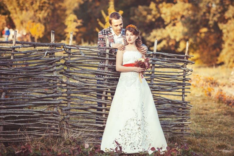 Newlyweds που στέκεται κοντά στον ψάθινο φράκτη στοκ εικόνες