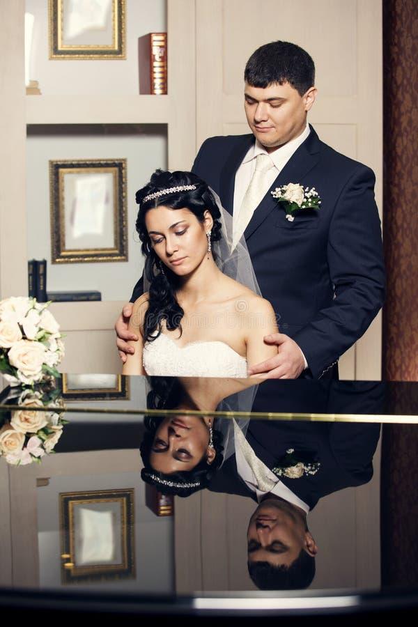 Newlyweds. Bride playing piano royalty free stock photography