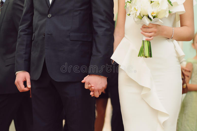 Newlyweds at Ceremony. Newlyweds holding hands at ceremony royalty free stock photography