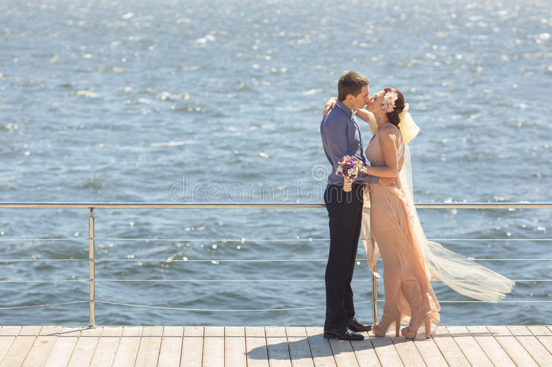 Newlyweds embracing and kissing stock images