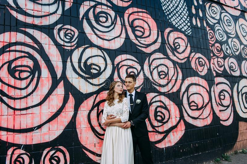 Newlyweds embracing next to graffiti wall. Young wedding couple stock photography