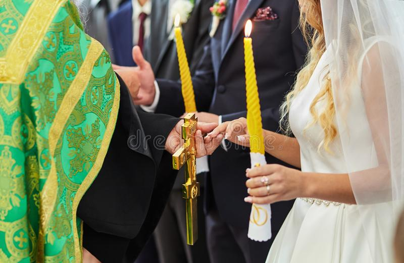 Newlyweds exchange wedding rings on a ceremony in the church stock image
