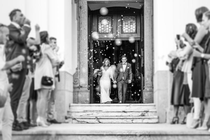 Newlyweds exiting the church after the wedding ceremony, family and friends celebrating their love with the shower of royalty free stock photography