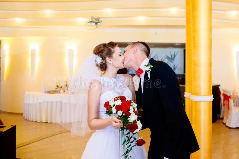 Newlyweds first kiss on wedding party. stock photos