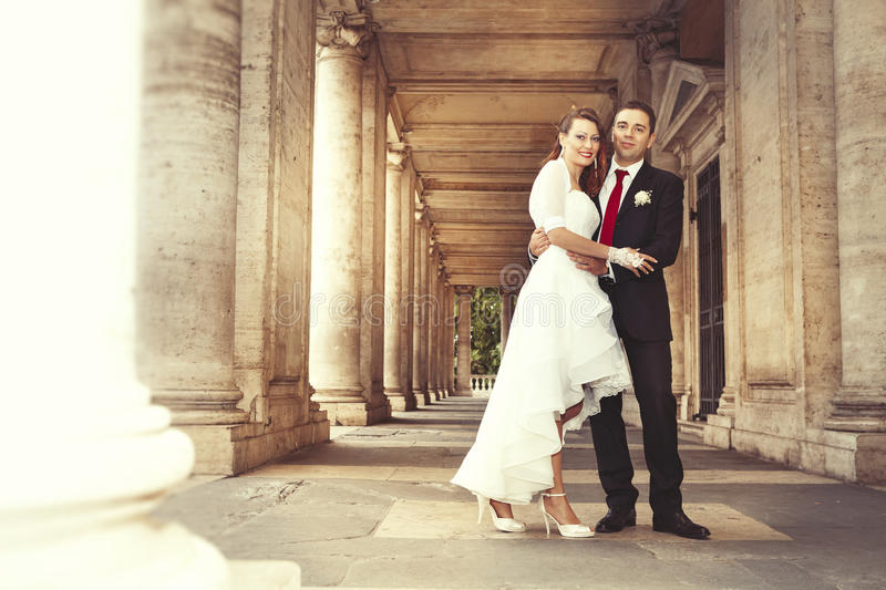 Newlyweds in the historic center of Rome. Ancient columns. royalty free stock photo