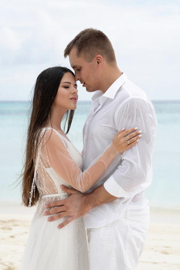 Newlyweds are hugging on a gorgeous beach with white sand and turquoise water royalty free stock photo