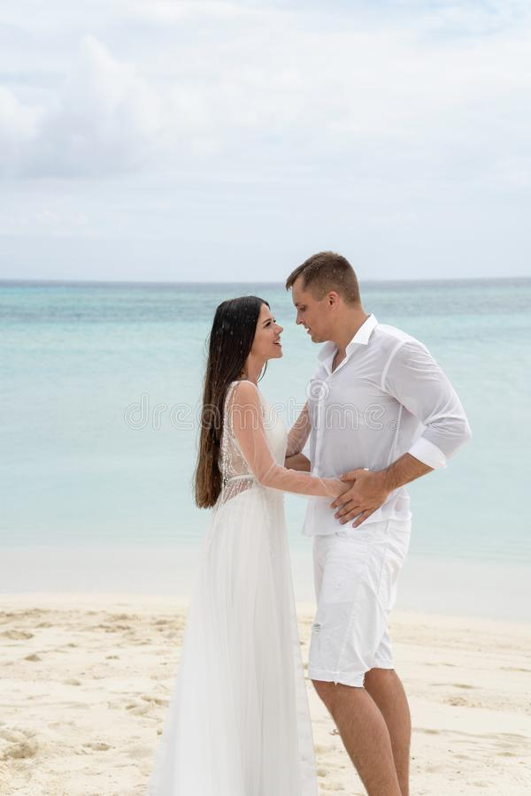Newlyweds are hugging on a gorgeous beach with white sand and turquoise water stock photo