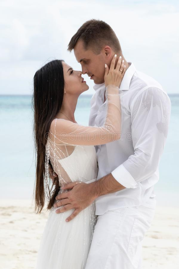 Newlyweds are hugging on a gorgeous beach with white sand and turquoise water royalty free stock photography