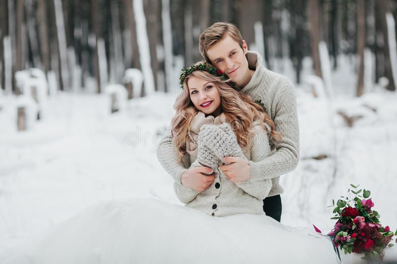 Newlyweds are hugging in the winter forest. Couple in love. Winter wedding ceremony. stock images
