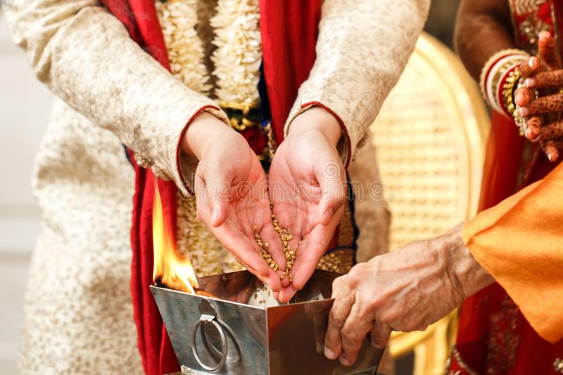 Indian wedding traditions. Bride and groom pour rice into the fire stock photography