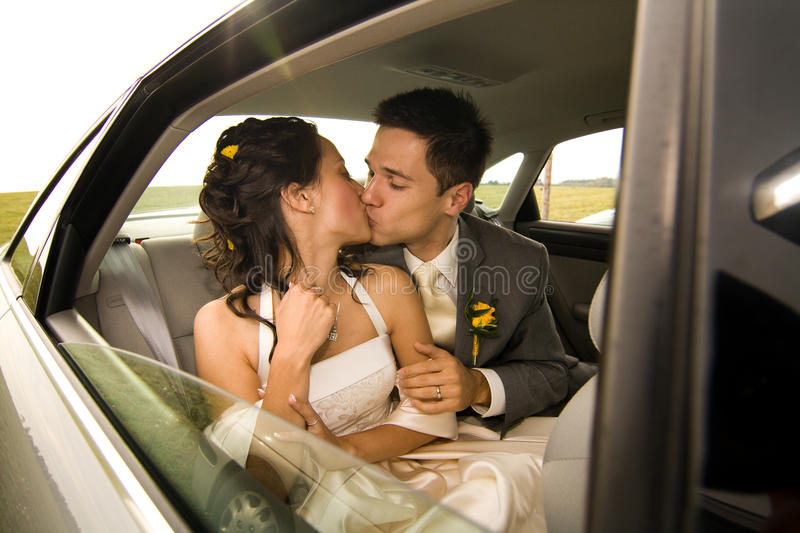 Newlyweds kissing in limo stock photography