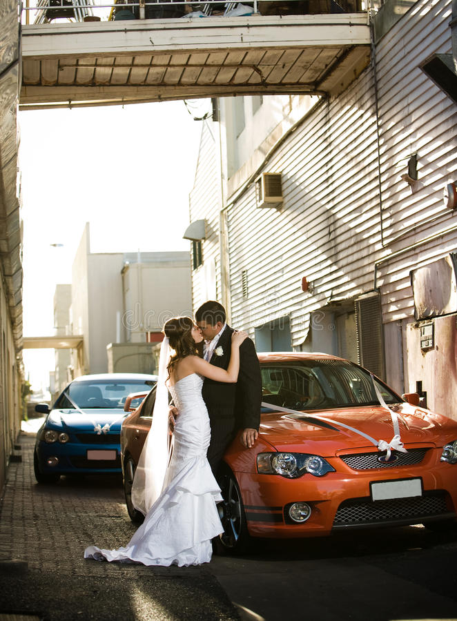 Newlyweds kissing passionately in alley stock images