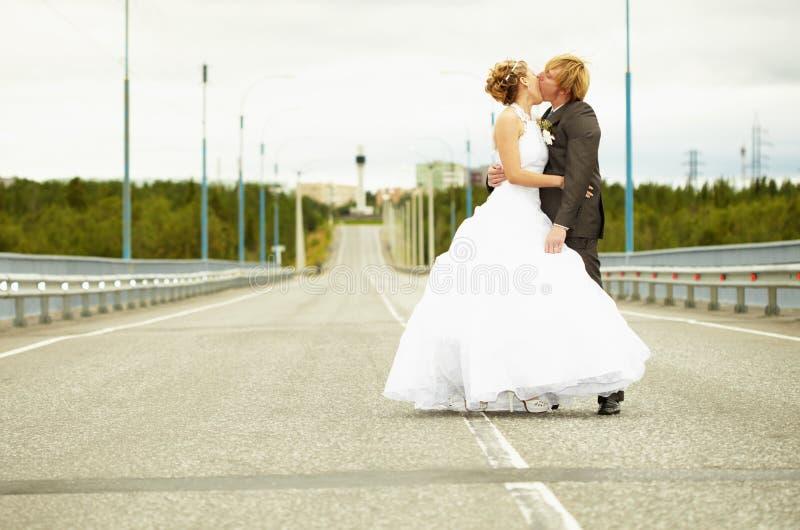 Newlyweds kissing passionately on highway royalty free stock image