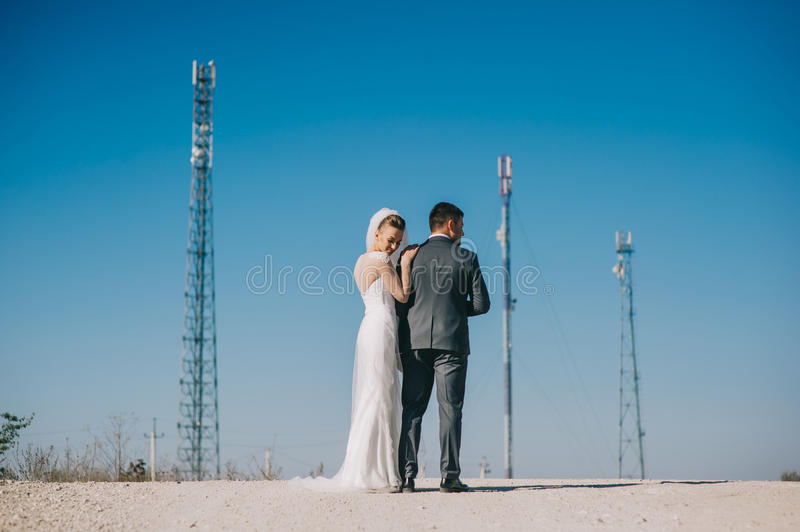 Newlyweds kissing passionately while standing on the highway stock photo